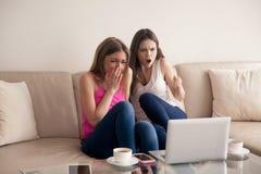 Deux amies effrayées criant tout en observant le film d'horreur Photos stock