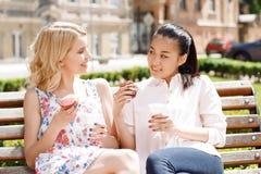 Deux amies en parc avec du café et des petits gâteaux Images libres de droits