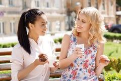 Deux amies en parc avec du café et des petits gâteaux Photographie stock libre de droits