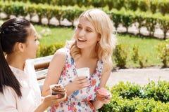 Deux amies en parc avec du café et des petits gâteaux Photographie stock