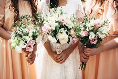 Deux amies et une jeune mariée tiennent de beaux bouquets de mariage dans t Photos libres de droits