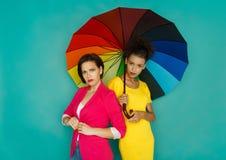 Deux amies fâchées posant au fond de studio d'azur Image stock