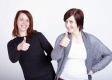 Deux amies faisant des gestes le pouce  Image stock