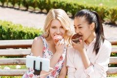 Deux amies faisant le selfie avec des petits gâteaux Images libres de droits