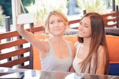Deux amies faisant le selfie en café Photo stock