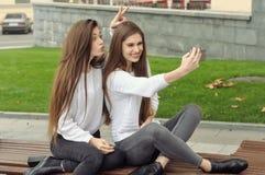 Deux amies font la photo de selfie et montrent les klaxons Image stock