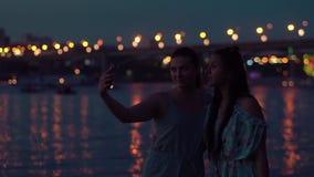 Deux amies font le selfie la nuit par la rivière contre le contexte des lumières Mouvement lent clips vidéos