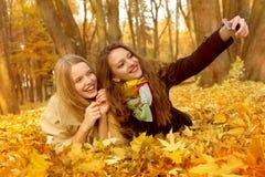 Deux amies font un selphi sur une pile des feuilles en parc d'automne Photographie stock libre de droits