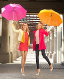 Deux amies gaies sautant avec des parapluies Image libre de droits