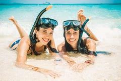 Deux amies heureuses avec le masque naviguant au schnorchel appréciant sur la plage Image libre de droits