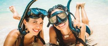 Deux amies heureuses avec le masque naviguant au schnorchel appréciant sur la plage Images libres de droits