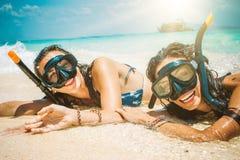 Deux amies heureuses avec le masque naviguant au schnorchel appréciant sur la plage Photos stock