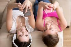 Deux amies heureuses dans des écouteurs appréciant leur musique préférée Images stock