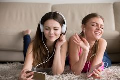 Deux amies heureuses dans des écouteurs appréciant leur musique préférée Photos stock