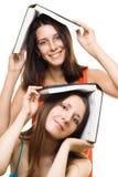 Deux amies heureuses de femmes avec des livres jouent et sourient Photographie stock
