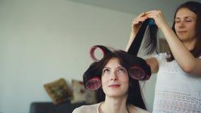 Deux amies heureuses de femmes font à coiffure de bigoudi d'amusement et ont l'amusement à la maison Photos libres de droits