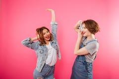 Deux amies heureuses de femmes font la photo par l'appareil-photo Image stock