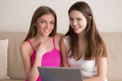 Deux amies heureuses ensemble utilisant l'ordinateur portable à la maison Photo stock