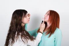 Deux amies heureuses faisant le maquillage entre eux Photos libres de droits