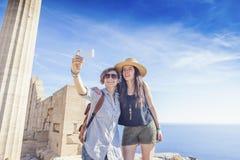 Deux amies heureuses faisant le selfie contre la mer et le Gree Photo stock