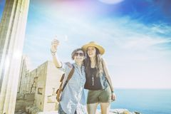 Deux amies heureuses faisant le selfie contre la mer et le Gree Photographie stock
