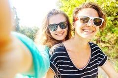 Deux amies heureuses faisant le selfie dehors Photos stock