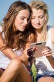 Deux amies heureuses lisant le courrier intéressant sur le comprimé photos stock