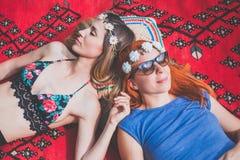 Deux amies hippies se reposant sur la couverture dehors Photographie stock libre de droits