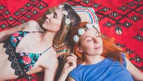 Deux amies hippies se reposant sur la couverture dehors Photos stock