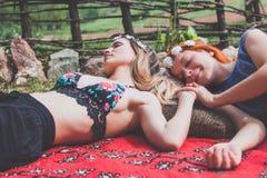 Deux amies hippies se reposant sur la couverture dehors Photo libre de droits