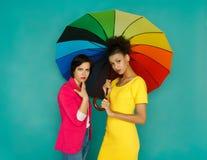 Deux amies inquiétées posant au fond de studio d'azur Images stock