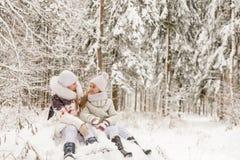 Deux amies jouant dans une forêt d'hiver Photographie stock