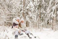 Deux amies jouant dans une forêt d'hiver Image libre de droits