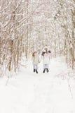 Deux amies jouant dans une forêt d'hiver Photos libres de droits