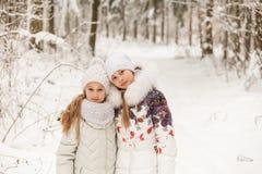 Deux amies jouant dans une forêt d'hiver Images libres de droits