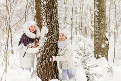 Deux amies jouant dans une forêt d'hiver Photos stock