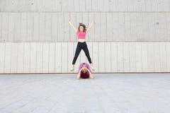 Deux amies jouant ensemble et sautant sur l'un l'autre Photographie stock libre de droits