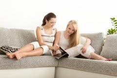 Deux amies lisant la revue de mode au sofa Photo stock