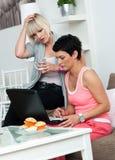 Deux amies mûres de femme avec l'ordinateur portatif à la maison Photographie stock libre de droits
