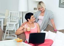 Deux amies mûres de femme avec l'ordinateur portatif à la maison Images stock