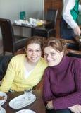 Deux amies mangeant des gâteaux et parlant en café Image libre de droits