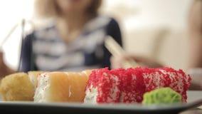 Deux amies mangeant des petits pains avec des baguettes pendant le dîner au restaurant cuisine japonaise en gros plan clips vidéos