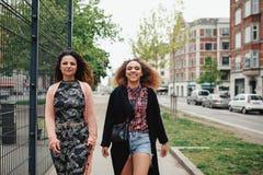 Deux amies marchant le long de la rue de ville Photographie stock libre de droits