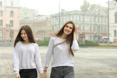 Deux amies marchent autour de la place tenant des mains Image libre de droits