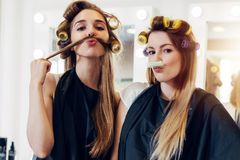 Deux amies mignonnes dans des bigoudis de port de cap noir fabriquant la moustache à partir de leurs cheveux et rouleau dans le s Photo stock