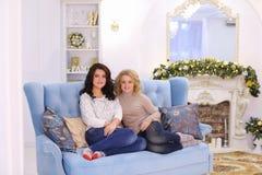 Deux amies mignonnes posant avec le sourire et s'asseyant ensemble sur c Images stock