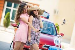 Deux amies mignonnes prenant des selfies près de la voiture Image libre de droits