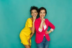 Deux amies montrant le symbole de silence au fond de studio d'azur Photographie stock