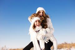 Deux amies ont l'amusement et apprécient la neige fraîche Image libre de droits