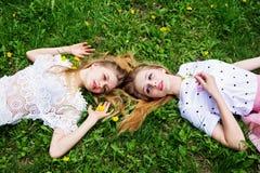 Deux amies ont un repos sur l'herbe photographie stock libre de droits
